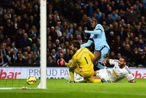 Manchester City's Yaya Toure scores his teams second goal past Swansea City goalkeeper Lucasz Fabianski and Swansea City's Kyle Bartley (right). Photo credit: Martin Rickett/PA Wire