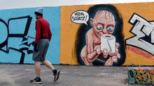 """COVETED: A man passes graffiti on a Berlin wall showing 'Lord of the Rings' character Gollum with a toilet roll and a speech bubble reading """"My Precious"""". Photo: Reuters"""