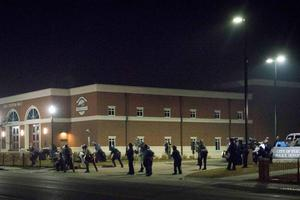 """Police stand guard moments after gun shots were fired outside the City of Ferguson Police Department and Municipal Court in Ferguson, Missouri, early March 12, 2015. Two police officers were shot during a protest outside the Ferguson, Missouri police department early on Thursday, the St. Louis Post-Dispatch newspaper reported. The newspaper reported that Ferguson Lt. Col. Al Eickhoff said he did not believe either of the officers were part of his department. He could not provide details on their injuries to the Post-Dispatch. A few dozen demonstrators fled following the sound of gunfire around midnight with some screaming, """"They hit a cop,"""" according to a Reuters photographer at the scene. Police could not be reached immediately for comment. REUTERS/Kate Munsch  (UNITED STATES - Tags: CIVIL UNREST CRIME LAW POLITICS TPX IMAGES OF THE DAY)"""