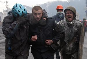Anti-government protesters detain a wounded policeman (C) during clashes in the Independence Square in Kiev. Fresh fighting broke out in central Kiev on Thursday, shattering a truce declared by Ukrainian President Viktor Yanukovich, as the Russian-backed leader met European ministers demanding he compromise with pro-EU opponents. Reuters