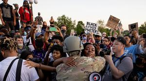 National Guard Master Sgt, Acie Matthews Jr. hugs a protester at the State Capitol in St. Paul, Minn., Monday, June 1, 2020, during protests over the death of George Floyd. (Carlos GonzalezStar Tribune via AP)