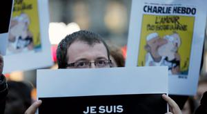"""A man holds a placard which reads """"I am Charlie"""" to pay tribute during a gathering at the Place de la Republique in Paris. Reuters/Gonzalo Fuentes"""