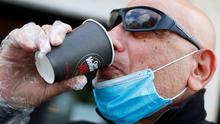 A man wearing a protective face mask and glove drinks a coffee, as Italy begins a staged end to its nationwide lockdown. Photo: REUTERS/Guglielmo Mangiapane