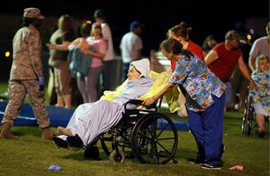 Emergency workers assist an elderly person at a staging area at a local school stadium Wednesday, April 17, 2013, in West, Texas.