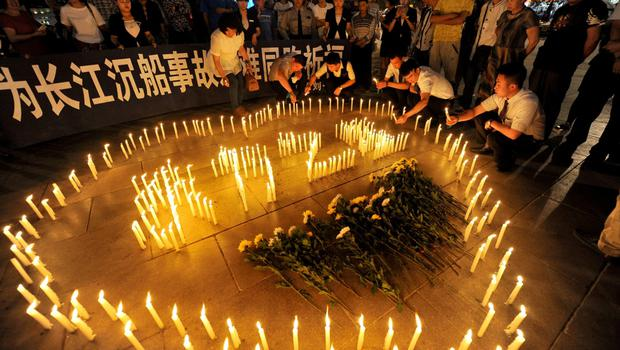 """People light candles to pray for victims of the Eastern Star cruise ship which capsized in the Jianli section of the Yangtze River, in Taiyuan, Shanxi province, June 7, 2015. The banner reads: """"Pray for the people killed in the capsized ship accident in the Yangtze."""" REUTERS/Stringer"""