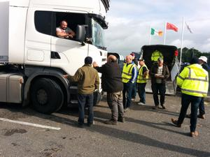Farmers talk to a trucker as they protest at the ABP beef plant in Bandon where a Chinese flag flies in the background. Photo: Denis Boyle