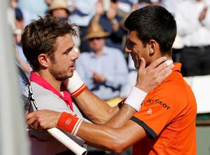 Stan Wawrinka of Switzerland (L) hugs Novak Djokovic of Serbia after winning their men's final match at the French Open tennis tournament at the Roland Garros stadium in Paris, France, June 7, 2015
