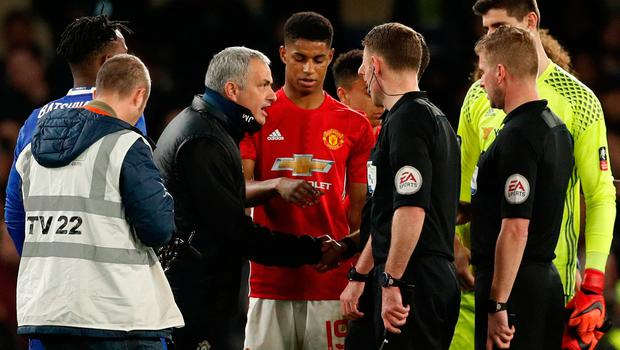 Manchester United manager Jose Mourinho talks with referee Michael Oliver as they shake hands after the match