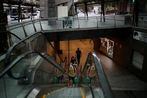 People wearing protective face masks use an escalator at a Sydney transit hub on Wednesday, as New South Wales begins shutting down non-essential businesses and moving toward harsh penalties to enforce self-isolation to avoid the spread of coronavirus disease. Photo: Rueters/Loren Elliott