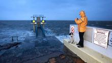 A walker and their dog pictured at the  Blackrock Diving tower near the Promenade in Galway as Storm Lorenzo tracked up the west coast of Ireland. Picture Credit:Frank McGrath