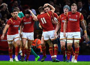 Wales' George North celebrates with teammates after scoring their first try
