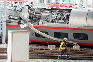 A recuer passes a derailed train in the station of Lucerne, Switzerland  (Urs Flueeler/Keystone via AP)