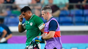 Bundee Aki of Ireland leaves the pitch for a head injury assessment against Scotland