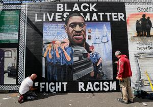 Artists Lyonsie (left) and Micky Doc put the finishing touches to a mural to George Floyd at Belfast's International Wall on the Falls Road. Photo: Brian Lawless/PA Wire