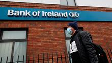 Face of the times: A man wearing a protective facemask walks past a Bank of Ireland branch in Dublin. Photo: Brian Lawless/PA Wire