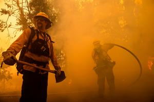 Firefighters battle the Kincade Fire along Chalk Hill Road in Healdsburg, California on October 27, 2019. Photo by Philip Pacheco / AFP