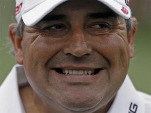 Angel Cabrera grimaces after sinking a birdie putt on the second green