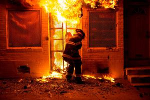 A firefighter uses a saw to open a metal gate while fighting a fire in a convenience store and residence during clashes after the funeral of Freddie Gray in Baltimore, Maryland in the early morning hours of April 28, 2015. REUTERS/Eric Thayer