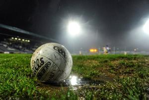 A match ball sits on the field during a wet night