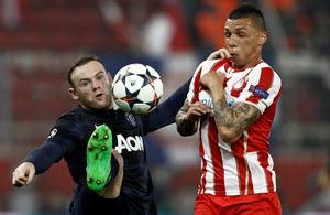 Manchester United's Wayne Rooney (L) fights for the ball with Olympiakos' Jose Holebas during their Champions League round of 16 first leg soccer match at Karaiskaki stadium in Piraeus, near Athens, February 25, 2014.    REUTERS/Yorgos Karahalis (GREECE - Tags: SPORT SOCCER)