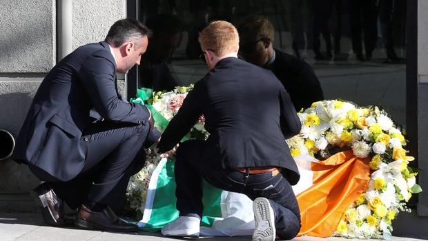 Philip Grant, Consul General of Ireland to the Western United States (L) helps Neil Sands, President of the Irish Network Bay Area, lay an Irish flag atop two wreaths at the scene of a 4th-story apartment building balcony collapse in Berkeley, California June 16, 2015. REUTERS/Elijah Nouvelage