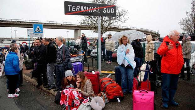 Travelers wait outside the Orly airport , south of Paris, Saturday, March, 18, 2017. A man was shot dead after wrestling a soldier to the ground at Paris' Orly Airport and trying to take her rifle, officials said. No one else in the busy terminal was hurt, but thousands of travelers were evacuated and flights were diverted to the city's other airport. (AP Photo/Thibault Camus)