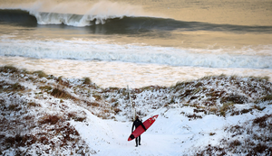 Pro surfer Alastair Mennie makes his way towards the beach at Portrush in County Antrim. Photo: Getty Images