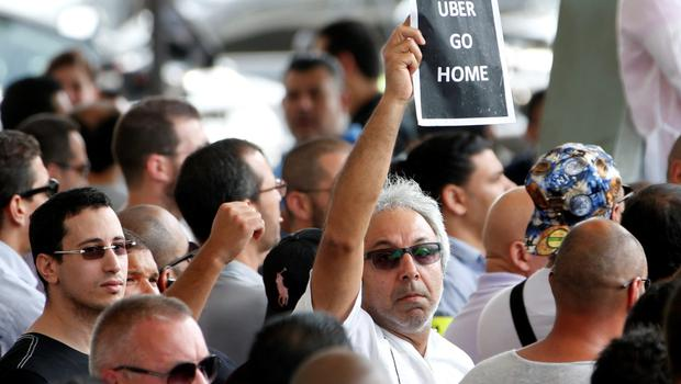 "A French taxi driver holds a leaflet which reads ""Uber go home"" as striking taxi drivers gather near the Paris ring road during a national protest against car-sharing service Uber, in Paris, France, June 25, 2015. French taxi drivers stepped up protests against U.S. online cab service UberPOP on Thursday, blocking road access to airports and train stations in Paris and other cities.  REUTERS/Charles Platiau"