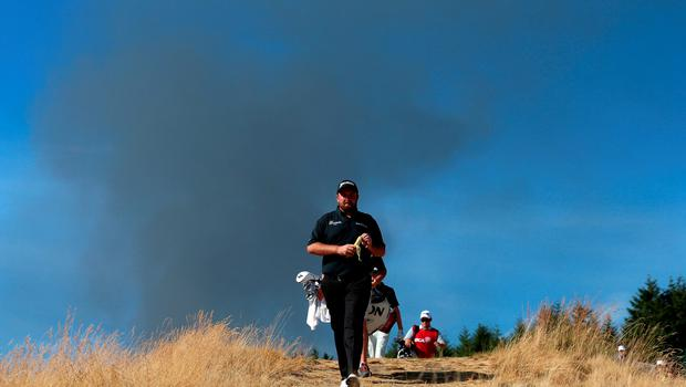 UNIVERSITY PLACE, WA - JUNE 20:  Shane Lowry of Ireland walks the 15th hole as smoke from a nearby fire is seen in the distance during the third round of the 115th U.S. Open Championship at Chambers Bay on June 20, 2015 in University Place, Washington.  (Photo by Andrew Redington/Getty Images)