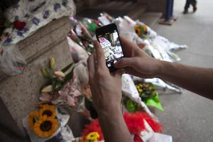 A man takes photos of cards, flowers and photos, which were left in tribute as part of a makeshift memorial on the steps in front of Joan Rivers' former residence in the Manhattan borough of New York September 6, 2014.   REUTERS/Carlo Allegri