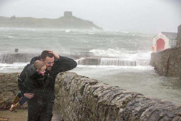Aaron and Lucia Kavanagh brave Storm Brendan at Coliemore Harbour, Dalkey. Photo: Mark Condren