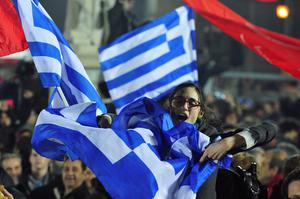 A woman waves a Greek flag during a speech by the leader of Syriza left-wing party Alexis Tsipras outside Athens University Headquarters, Sunday, Jan. 25, 2015