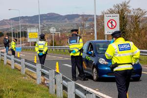Garda stop and check vechicles at the border crossing at Carrkcarnon, County Louth, under new powers to curb non-essential travel during the coronavirus crisis. (Photo by PAUL FAITH / AFP) (Photo by PAUL FAITH/AFP via Getty Images)
