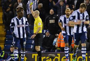 West Bromwich Albion's Nigerian striker Victor Anichebe (L) is shown the yellow card by referee Anthony Talyor after celebrating scoring an equalising goal in the crowd