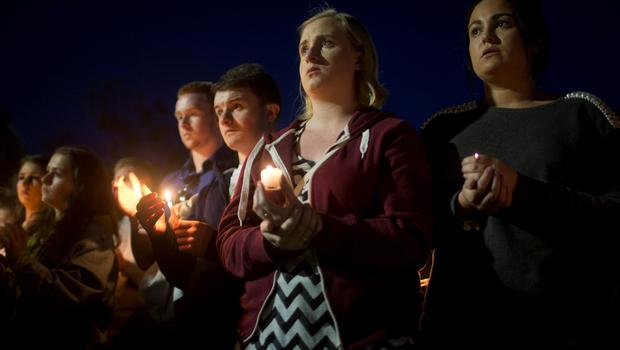 Mourners hold candles during a vigil for six Irish students Wednesday, June 17, 2015, in Berkeley, Calif. (AP Photo/Beck Diefenbach)