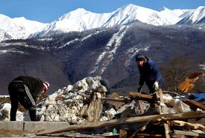 Workers start cleaning the area next to an unfinished hotel in the mountain media village on top of the village of Esto Sadok at the Rosa Khutor alpine resort near Sochi