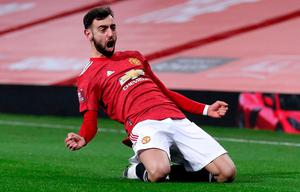 Bruno Fernandes slides in celebration after his late free-kick secured a place in the FA Cup fifth round for Manchester United. Photo: Getty Images
