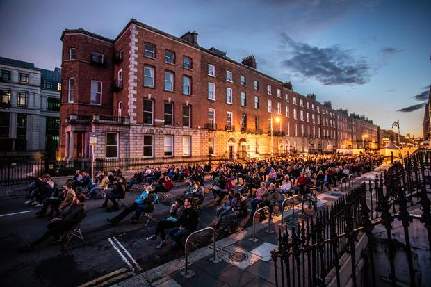 A socially distanced audience watches musician Lisa Hannigan perform outside on Mount Street in Dublin