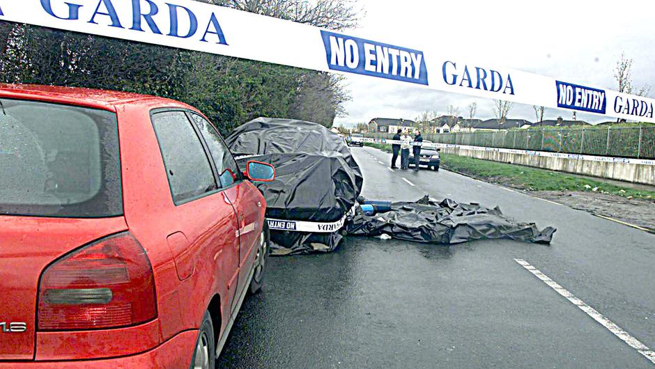 Gunned down: The body of Jonathan O'Reilly lies on the road where he was shot dead outside Cloverhill prison
