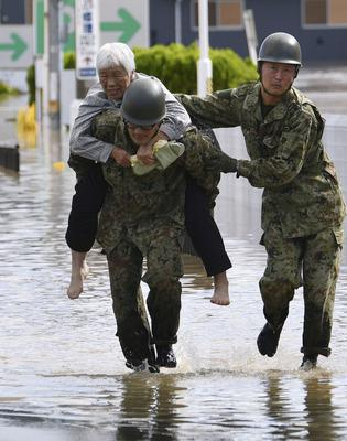 A local resident is rescued by Japanese Self-Defence Forces soldiers from areas flooded by Abukuma river following Typhoon Hagibis in Motomiya, Fukushima prefecture, Japan, October 13, 2019, in this photo taken by Kyodo. Mandatory credit Kyodo/via REUTERS