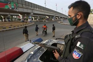 Pakistani police officers stop travellers after a government announced to lockdown the city due to concerns over the spread of the new coronavirus, in Karachi (AP Photo/Fareed Khan)