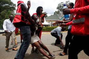 A relative is assisted by Kenya Red Cross staff as she reacts where bodies of the students killed in Thursday's attack by gunmen are preserved at the Chiromo Mortuary in the capital Nairobi April 5, 2015.  REUTERS/Gregory Olando