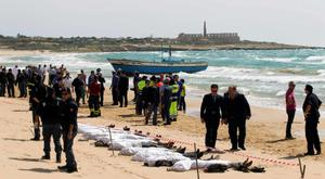 Rescue workers stand next to bodies of migrants who drowned on the beach in the Sicilian village of Sampieri September 30, 2013. At least 13 people on a migrant boat arriving in Sicily drowned close to the coast near the eastern city of Ragusa, apparently after trying to disembark from their stranded vessel, Italian authorities said on Monday. Officials said the boat was carrying around 250 people but there was no immediate word on where they came from.  REUTERS/Gianni Mania (ITALY - Tags: DISASTER)