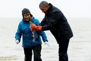 A fish apparently spawns, relieving itself on U.S. President Barack Obama (R) as he meets a  traditional fisherman on the shore of the Nushagak River in Dillingham, Alaska September 2, 2015. After meeting tribal leaders and fishermen in Dillingham, home to one of the world's largest sockeye salmon fisheries, Obama will fly into Kotzebue, an Arctic town of about 3,000 that is battling coastal erosion caused by rising seas. REUTERS/Jonathan Ernst
