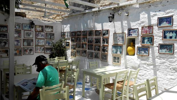 A man reads a newspaper while sitting in a taverna at the island of Paros, Greece June 26, 2015. A rise in consumer taxes on Greek islands' goods and services is one of the sacrifices creditors are seeking from Athens to unlock bailout funds that will allow Greece to remain in the euro. The tax hike is one of the sticking points thwarting a deal and prompting Prime Minister Alexis Tsipras to call a July 5 referendum on the bailout terms. Yet even before the vote, Greece is likely to default on a debt payment, setting off a financial crisis that could damage an upcoming tourist season expected to be one of the most vibrant in years. Picture taken June 26, 2015.  REUTERS/Matthias Williams