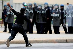 A man throws a brick at police following the funeral of Freddie Gray in Baltimore. Photo: AP