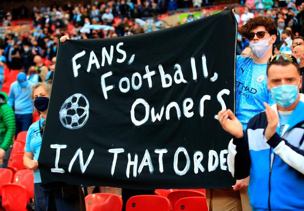 """Fans hold up a banner protesting against the European Super League ahead of the Carabao Cup Final at Wembley Stadium, London. Picture date: Sunday April 25, 2021. PA Photo. The 2021 Carabao Cup Final has been confirmed as an official test event for the UK Government's Events Research Programme with 8,000 people permitted to attend Wembley Stadium. See PA story SOCCER Final. Photo credit should read: Adam Davy/PA Wire.  RESTRICTIONS: EDITORIAL USE ONLY No use with unauthorised audio, video, data, fixture lists, club/league logos or """"live"""" services. Online in-match use limited to 120 images, no video emulation. No use in betting, games or single club/league/player publications."""