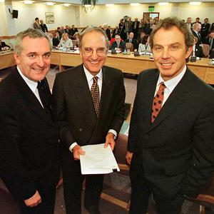 Bertie Ahern, George Mitchell and Tony Blair, smiling after they signed the historic Good Friday Agreement.