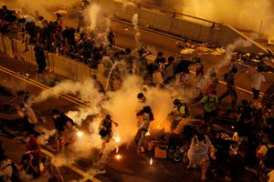 Riot police fire teargas to disperse protesters after thousands of demonstrators blocked the main street to the financial Central district outside the government headquarters in Hong Kong September 29, 2014
