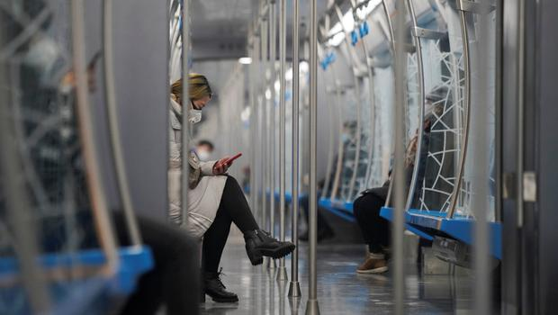 A passenger wearing a face mask checks her mobile phone while riding the subway as the country is hit by an outbreak of the novel coronavirus, in Beijing, China. REUTERS